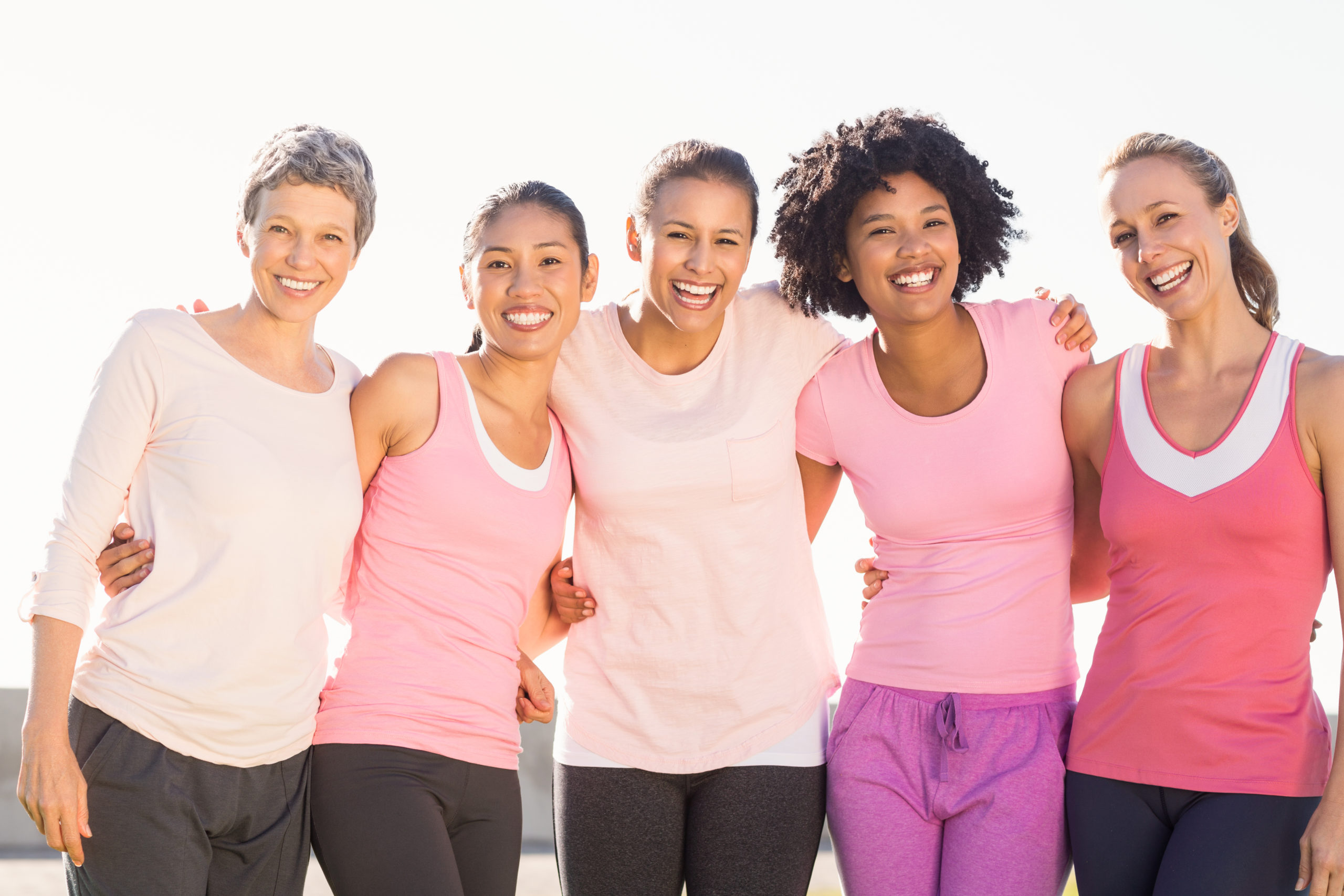 Five women wearing pink athletic wear clothes and all are smiling